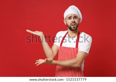 Perplexed young bearded male chef cook or baker man in striped apron white t-shirt toque chefs hat posing isolated on red background. Cooking food concept. Mock up copy space. Pointing hands aside #1521537779