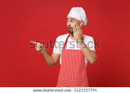 Shocked chef cook baker man in striped apron white t-shirt toque chefs hat posing isolated on red background. Cooking food concept. Mock up copy space. Pointing index fingers aside put hand on cheek #1521537791