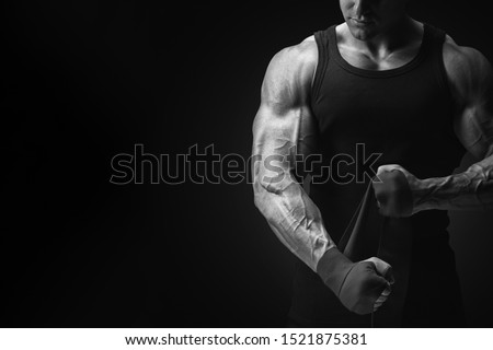 Bodybuilder fitness lifestyle concept Croped black and white shot on black background Man is wrapping hands with boxing wraps isolated Strong hands and fist, ready for training and active exercise Royalty-Free Stock Photo #1521875381