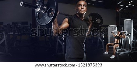 Sport, bodybuilding, lifestyle and people concept. Young and fit couple in the gym doing workout. Group of women and men bodybuilders training on special sport equipment in the gym.  #1521875393