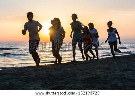 Group of People Running on the Beach at Sunset #152193725