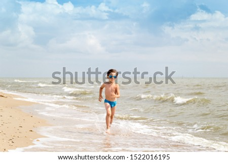 A boy in sunglasses runs along the sea coast on golden sand. Rest of children on summer vacation. Holiday background with copy space. Front view. #1522016195
