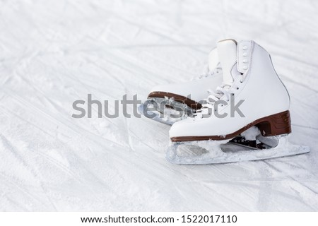 close up of white leather figure skates and copy space over ice background with marks from skating