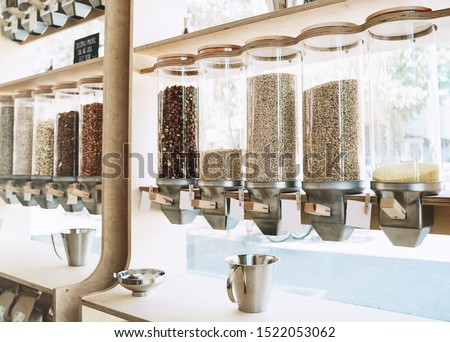 Eco-friendly zero waste shop. Dispensers for cereals, nuts and grains in sustainable plastic free grocery store. Bio organic food. Shopping at small local businesses. New trend alternative buying Royalty-Free Stock Photo #1522053062
