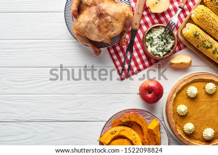 top view of roasted turkey, pumpkin pie and grilled corn served on white wooden table with red plaid napkin #1522098824