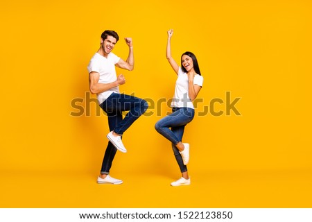 Full body photo of pair lady and guy fans supporting favorite football team raising fists wear casual outfit isolated yellow color background #1522123850