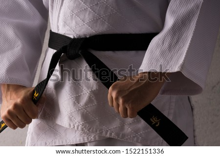 judo fighter poses in white kimono with black belt. Japanese judo and  jiu jitsu Royalty-Free Stock Photo #1522151336
