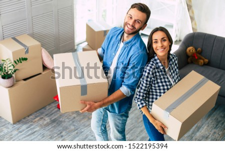 Couple in new home. Young attractive couple is excited about their new house and are willing to furnish it together, making all the best to create a lovely home atmosphere. #1522195394