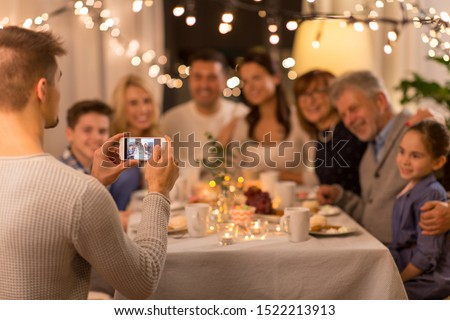 celebration, holidays and people concept - man with smartphone taking picture of family at dinner party #1522213913