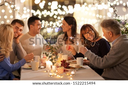 celebration, holidays and christmas concept - happy family with sparklers having fun at dinner party at home #1522215494