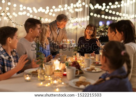 dinner party and celebration concept - happy family with cake celebrating grandmothers birthday at home #1522215503