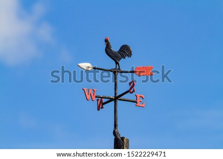 Cockerel Rooster weather vane, wind vane, weathercock against blue sky. Cast iron wind direction instrument, with letters for compass points, painted black red and white. Dublin, Ireland #1522229471