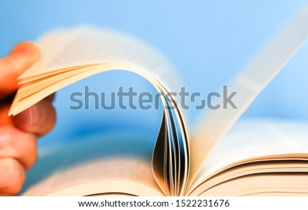 Hand flipping through pages of a book. Book pages turning #1522231676