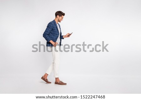 Full length body size view of nice attractive trendy cheerful cheery businessman wearing blue checked blazer using cell reading news feed reviewing feedback isolated over light white pastel background
