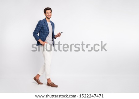 Full length body size view of nice attractive stylish trendy luxury cheerful cheery businessman wearing blue checked blazer using cell reading news feed isolated over light white pastel background