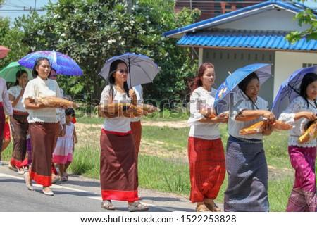 Buriram / Thailand-Sep 29, 2019: People hold set of monk's robes to offer monks in Sandonta tradition; Thai Khmer at Plabpla Chai village, Buriram, Thailand . #1522253828