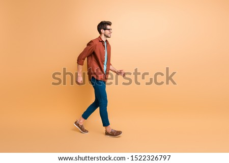 Full length body size profile side view of his he nice attractive trendy cheerful cheery brunette guy business assistant agent broker walking isolated over beige color pastel background #1522326797