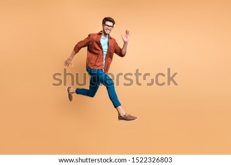 Full length body size view of his he nice attractive cheerful cheery glad active successful guy leader jumping in air running fast hurry-up meeting isolated over beige color pastel background #1522326803