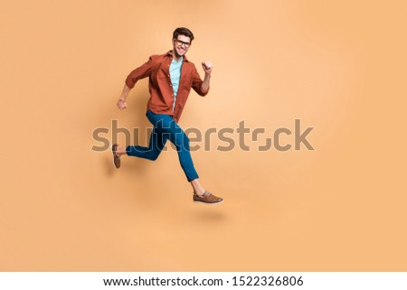 Full length body size view of nice attractive cheerful cheery strong sportive successful guy leader jumping in air running fast hurry-up meeting appointment isolated over beige color pastel background #1522326806