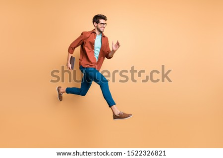 Full length body size view of his he nice attractive cheerful glad guy leader jumping in air carrying laptop running fast late hurry-up meeting appointment isolated over beige color pastel background #1522326821