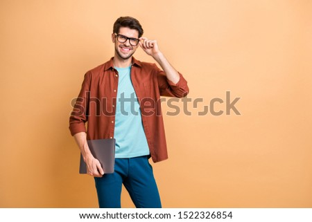 Portrait of his he nice attractive cheerful cheery successful content brunet guy holding in hands carrying laptop posing touching specs isolated over beige color pastel background