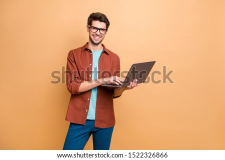 Portrait of his he nice attractive cheerful cheery successful content smart clever brunet guy agent broker holding in hands laptop working isolated over beige color pastel background