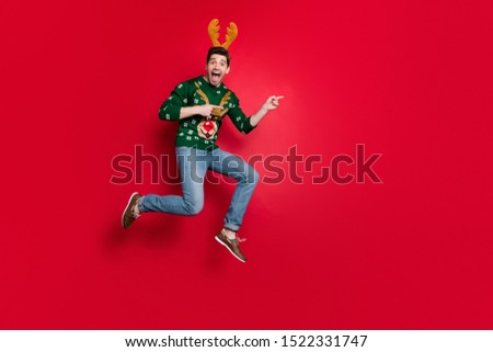 Full size photo of funny jumping guy direct fingers empty space advising go sale prices shopping wear pullover with ugly ornament isolated red color background #1522331747