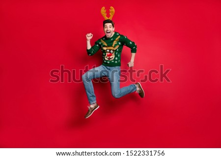 Full length photo of funky guy jumping high running fast to x-mas discounts shopping wear pullover with ugly deer ornament isolated red color background #1522331756