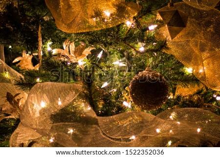 Gold Christmas pic Decoration. Ornaments, Lights, Gold net ribbon, fir tree. Concept Celebrating holidays.
