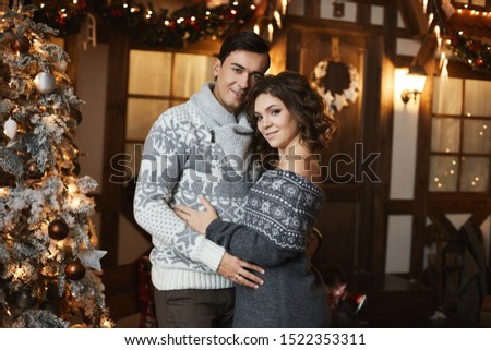 Beautiful couple of lovers in Scandinavian sweaters at New year interior. Sexy model girl and handsome man hugging together. A lovable young woman spending Christmas time with her husband. #1522353311