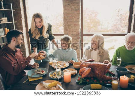 Happy thanksgiving! Photo of big family gathering sit feast meals dinner table wife giving everybody fresh baked bread multi-generation in evening living room indoors
