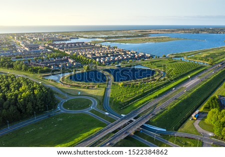 Modern sustainable neighbourhood in Almere, The Netherlands. The city heating (stadswarmte) in the district is partially powered by a solar panel island (Zoneiland). Aerial shot. #1522384862
