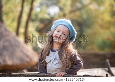 Portrait of a beautiful little girl in a blue beret. A child walks in a beautiful autumn park. #1522407134