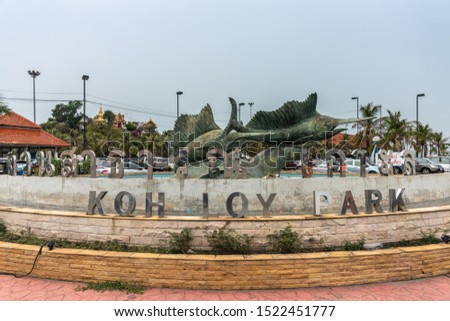 Si Racha, Thailand - March 16, 2019: Koh Loy Park sign at fountain with large bronze statues of swordfishes under blue sky with green foliage and red roof in back. #1522451777