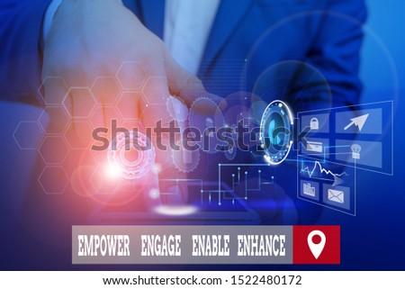 Handwriting text writing Empower Engage Enable Enhance. Concept meaning Empowerment Leadership Motivation Engagement Male human wear formal work suit presenting presentation using smart device.