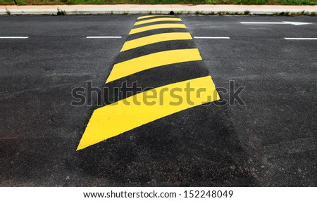 A yellow stripe speed ramp on an asphalt road.  #152248049