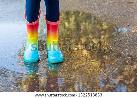 Kids in fall. close-up of a baby girls legs with rainbow rubber boots jumping into a puddle on an autumn walk. Children have fun playing outdoors. Waterproof boots for little girl #1522513853