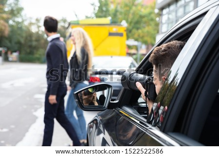Private Detective Taking Photos Of Man And Woman On Street #1522522586