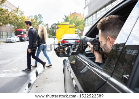 Private Detective Taking Photos Of Man And Woman On Street #1522522589