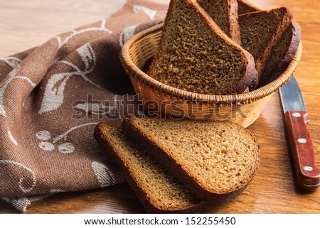 Sliced loaf of bread in bucket on wooden background. Selective focus. #152255450