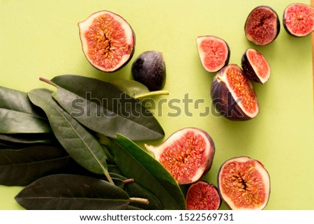 Ripe sweet figs. Fig fruit closeup macro. Healthy Mediterranean figs. The view from the top. Selective focus on the top slice of figs in the bowl. Vertical photo. green background. #1522569731