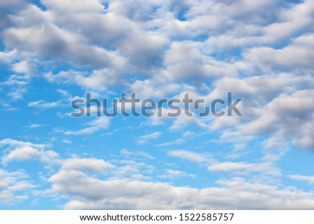 clouds of an average tier high cumulus, on a blue background of the sky #1522585757