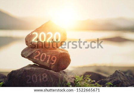 Number 2020  on stone the beach at sunrise. Concept Happy new year. #1522665671