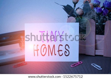Text sign showing Tiny Homes. Conceptual photo houses contain one room only or two and small entrance Cheap Flowers and writing equipments plus plain sheet above textured backdrop.