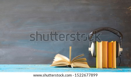 audio book concept with open book, row of books and headphones, panorama format on grungy background, good copy space