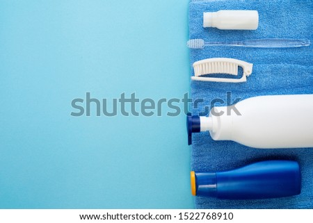 White shampoo bottle, baby soap, comb, towel, blue sunscreen bottle. Natural organic bath products. Bathroom items. Flat lay stock photo for web site and beauty blog. #1522768910