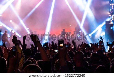 Music fan recording video on phone in crowd on concert, rear back view of audience people fans raise hands enjoy live music festival event shooting rock band stage on mobile device in purple lights