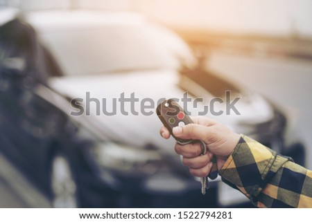 Close up hand of woman presses on the remote control car alarm systems or Car start stop system with finger pressing the button green or red, horizontal image.Technology, Car security system concept. #1522794281