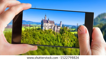 Neuschwanstein castle in Bavaria, Germany. Tourist taking photo of famous castle by mobile phone. Picture of mountain landscape with Neuschwanstein on smartphone. Travel and summer vacation concept.