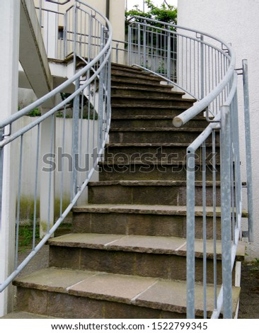 Outdoor staircase made of natural stone slabs and steel railing in coiled form,  #1522799345